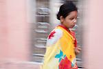 India, Jodhpur, Blue City, Historical City, Rajasthani woman wearing saree walking in old city, motion blur