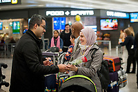 A family is united as passengers arrive from Dubai after a 14-hour flight on Emirates flight 231, at the international terminal at Dulles International Airport in Dulles, Va., Monday, March16, 2020. Some people are taking the precaution of wearing face masks as they arrive to be greeted by family and or friends. Credit: Rod Lamkey / CNP/AdMedia