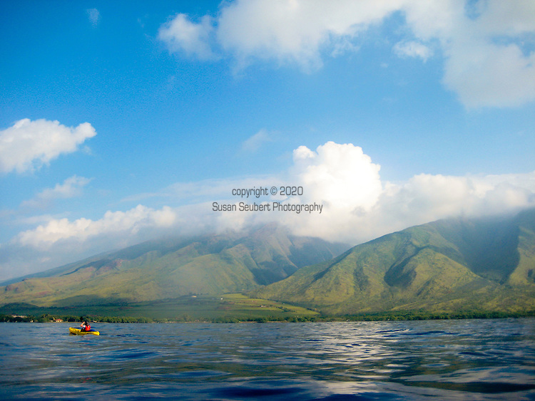 Kayakers off of the beach at Olowalu on West Maui during whale season at sunrise with the West Maui Mountains in the distance.