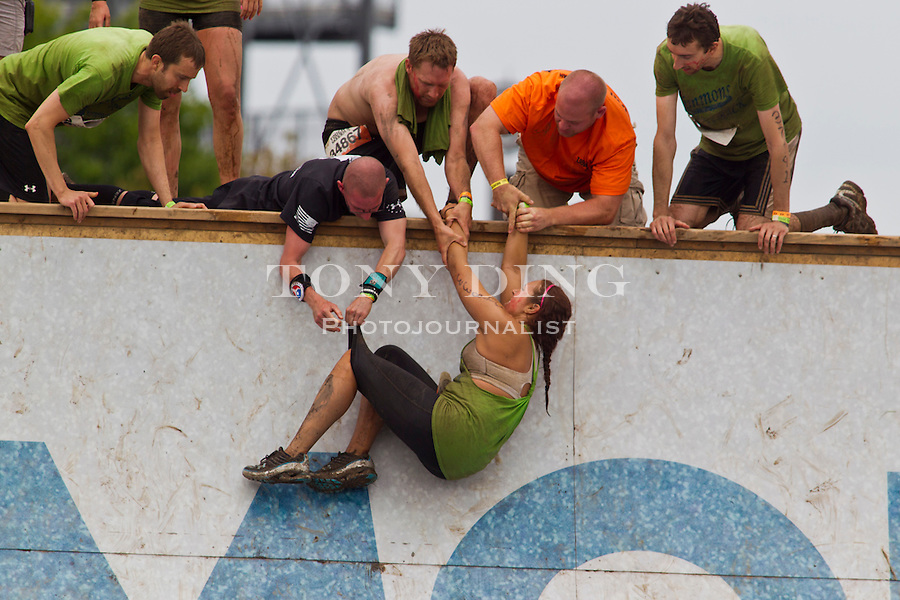 "16 April 2010: A competitor gets a hand and more help in attempting to climb up ""Everest"", one of twenty obstacles in the Tough Mudder adventure endurance race at Michigan International Speedway in Brooklyn, Michigan."