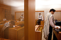 Men pray at Ohel Jakob synagogue on the opposite side of the chain link that separates men and women during worship. Each sect of Judaism has different rules and customs regarding interpretation of Jewish law.