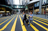 HONG KONG - APRIL 13: Two people cross the street in Central business district, on April 13, in Hong Kong. (Photo by Lucas Schifres/Pictobank)