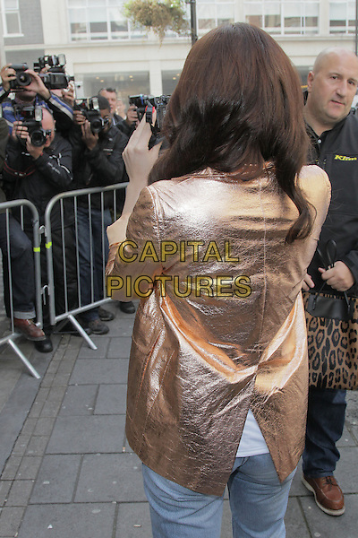 Jessie J (Jessica Ellen Cornish) at BBC Radio 1, London, England..September 27th, 2012.half length gold metallic shiny jacket  camera back behind rear taking picture photograph press photographers .CAP/HIL.©John Hillcoat/Capital Pictures.