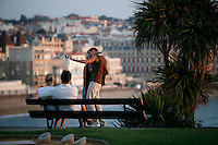 Young couple take a picture of themselves at sunset. Couples at a lookout point on the seaside town of Biarritz, France.