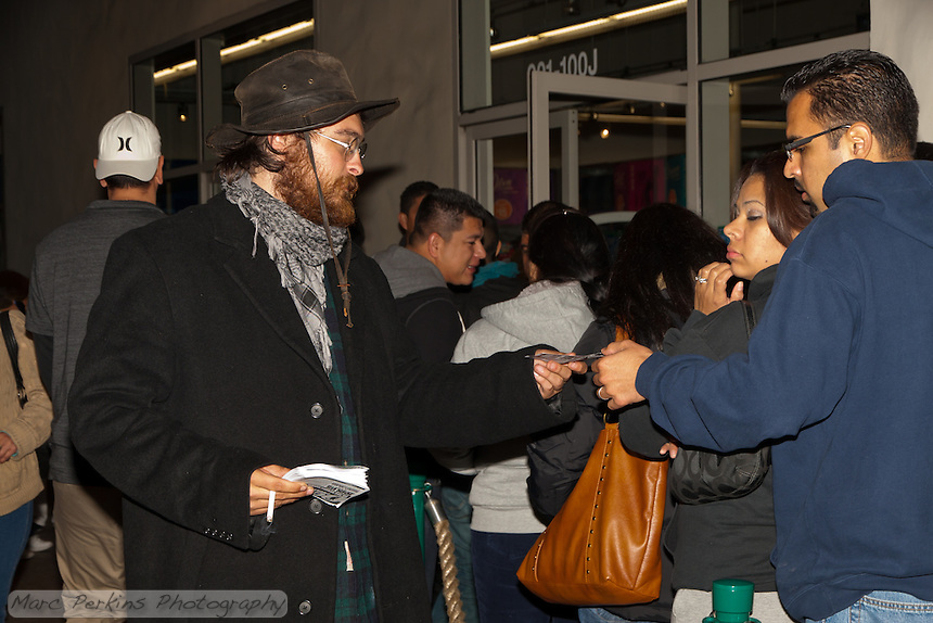 Justin H., an Occupy Orange County, Irvine protestor, hands out fliers to customers lined up at the Old Navy at South Coast Plaza early in the morning (12:47am) on Black Friday.