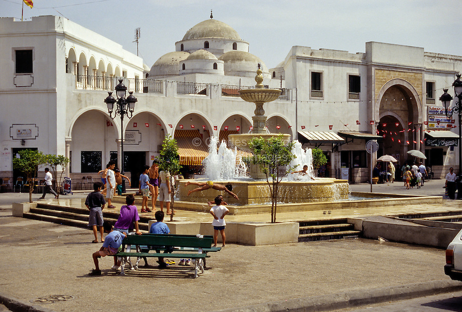 Tunis, Tunisia.  Sidi Mehrez Mosque (1675-92), from Place Bab Souika.  Children Playing in Neighborhood Fountain.  Bab Souika Entrance to the Medina on Right.