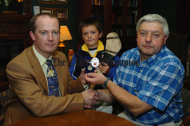 Clare Champion General manager John Galvin, makes a presentation to referee Seanie Mc Mahon after the Clare Champion Cup Final in Ennis watched by Seanie's son Páraic. Photograph by John Kelly.