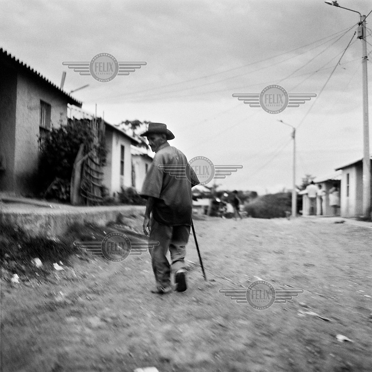 An elderly man walking through the slums of Sincelejo. Many Colombians are now living in slum areas after fleeing their homes due to political violence. This migration is part of the cycle of violence and forced internal displacement that affects large numbers of people.