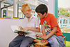 Two primary school boys reading book in library,