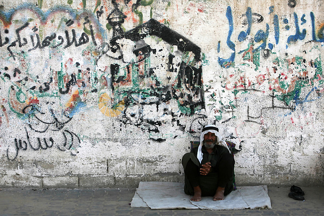 A Palestinian man sits outside his home in Rafah refugee camp, southern Gaza Strip, during Muslims fasting month of Ramadan, July 29, 2013. Ramadan is the holiest month in the Muslim calendar, during which people refrain from eating, drinking and smoking from sunrise to sunset. Photo by Eyad Al Baba