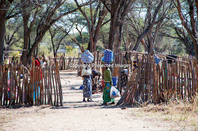 Vendors Carrying Wares on Head to Carry Home from Village Market in Rural Ziga.