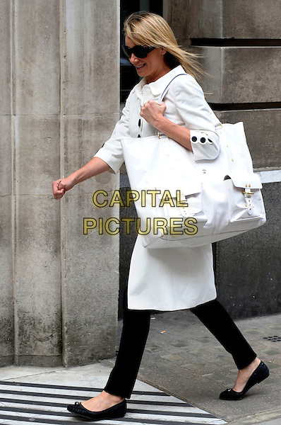 TAMZIN OUTHWAITE.Seen arriving at the BBC in a very white coat and matching handbag, London, England, UK, May 14th 2010..full length black buttons sunglasses trousers ballet pumps flats smiling overszied bag tote side walking .CAP/DYL.©Dylan/Capital Pictures.