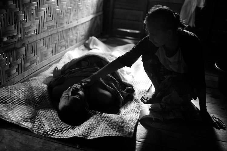 Beyond the Bullets - Death - ..A family member strokes the face of Kayog Kanapio, 53, during his funereal in the home of his relatives on June 2, 2009.  Kanapio had fled his home four times in the last two years and died of repertory failure while staying at an evacuation in Datu Gumbay, in the province of Maguindanao.  The shortage of food and medicine combined with the unsanitary living conditions claims the lives of many at the evacuation centers, while the actual fighting does little to either the Moro Islamic Liberation Front or the Armed Forces of the Philippines.