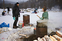 Ray Redington Jr. gets hot water made by the Takotna residents as Bill Pinham waits his turn at Takotna on Thursday morning