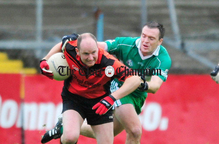 Ballyvaughan's Mark O' Loughlin holds off the challenge from Brendan Hughes of Wolfe Tones. Photograph by Declan Monaghan