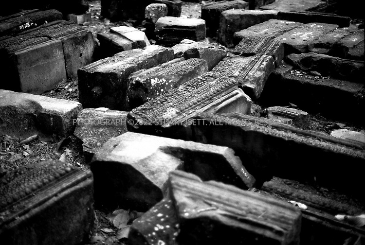 4/20/2003--Angkor Wat Temples, Siem Reap, Cambodia. ..Piles of stones at BAPHUON...North of the Golden Tower [Bayon]?. rises the Tower of Branze [Baphuon] higher even than the Golden Tower : a truly astonishing spectacle , with more than ten chambers at its base...Prasat Baphuon is located 200 metres (656 feet) northwest of the Bayon and south of Phimeanakas..A enter and leave at the east. It was built in middle of the 11th century (1060) by king Udayadityavarman II, dedicated to Siva (Hindu) with following Prasat Baphuon...BACKGROUND .The grandeur of Baphuon as described above by Zhou Daguan is unrecognizable today because of the poor condition of the temple. The French were in the process of restoring this temple when they were forced leave Angkor in 1972 because of war. Baphuon is situated inside the royal city of Angkor Thom but dates from the eleventh century and was built before the city was established. An interesting feature of Baphuon are the bas-reliefs which are scenes carved in small squares...Photograph by Stuart Isett.©2003 Stuart Isett