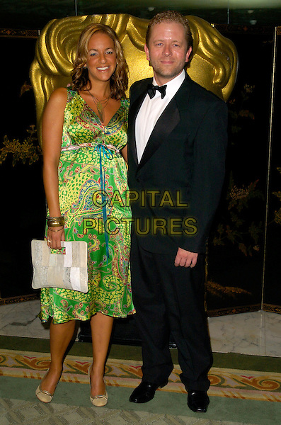 JON CULSHAW & GUEST.At the British Academy Television Craft Awards (BAFTA), the Dorchester, London, England..April 22nd, 2007.full length black tuxedo john bow tie green paisley dress beige purse bag .CAP/BEL.©Belcher/Capital Pictures