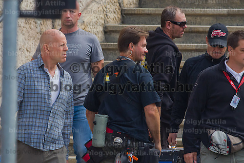 US actor Bruce Willis (L) is seen among members of the cast as he leaves the scene after a shooting day of the fifth piece in the Die Hard series titled Good Day to Die Hard during a shooting day in Budapest, Hungary on May 19, 2012. ATTILA VOLGYI