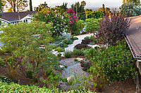 Rain garden with dry gravel percolation pond for rainwater captured from roof gutters, Erskin garden Water conserving Southern California front yard garden; design Urban Water Group