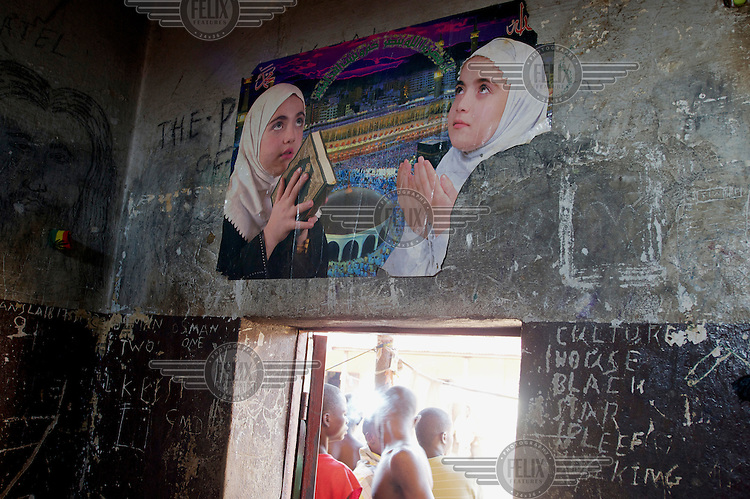 A poster of two Muslim girls praying beside a scene of the Hadj attached to a wall above the door of a cell in Bo Prison.