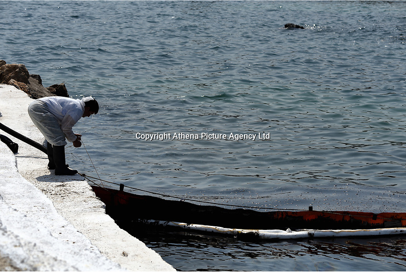 """Pictured: Specialist crew work to contain the oil spill that has reached the coast of Salamina, Greece<br /> Re: An oil spill off Salamina island's eastern coast is spreading and has become """"an environmental disaster"""" according to local authorities in Greece.<br /> The spill was caused by the sinking of the Aghia Zoni II tanker, carrying 2,200 metric tons of fuel oil and 370 metric tons of marine gas oil on Saturday, southwest of the islet of Atalanti near Psytalleia. According to reports, the coastline stretching from Kinosoura to the Selinia community has """"turned black"""" and authorities fear a new leak from the sunken ship.<br /> According to the island's mayor, Isidora Papathanasiou, the weather """"turned on Sunday afternoon and brought the oil spill to Salamina."""""""