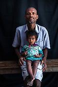 Bishun Sadah poses for a portrait with his 12 month grand-daughter, Lukho Sadah at the government health centre in Hanuman Nagar in Saptari, Nepal.