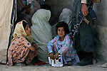 Women and children wait outside a police headquarters to receive free medical assistance, food staples and winter clothes from U.S. troops and Afghan police in Kandahar, Afghanistan. Aug. 18, 2008. DREW BROWN/STARS AND STRIPES