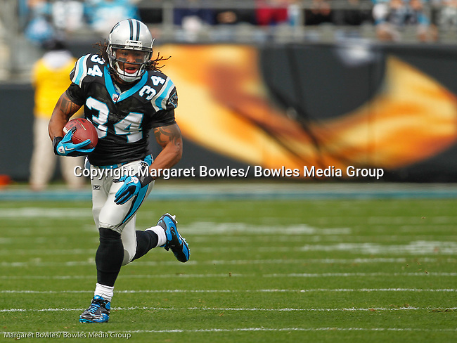 Carolina Panthers running back DeAngelo Williams (34) finds a hole in the defensive line during a game between the Panthers and the Tampa Bay Buccaneers.  The Panthers defeated the Buccaneers 48-16 on Dec. 24, 2011 in Charlotte, NC (AP Photo/Margaret Bowles)