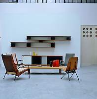 In the studio an elegant set of shelves is displayed above a sideboard, both by Jean Prouve, with an adjacent coffee table surrounded by a variety of armchairs