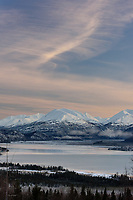 The Kenai Mountains and Skilak Lake are beautifully lit as the sun begins to set over a wintry Kenai Peninsula.