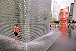 .CHICAGO, USA, AUGUST 26, 2004 : The Crown Fountain by spanish artist Jaume Plensa consist of two 50 feet high glass block towers at each end of a shallow pool. Each tower displays images and video portraits of Chicago residents. Every 12 minutes the faces purse their lips and spouts of water spew forth, to the delights of the children as the parents stand by. The Crown fountain was inaugurated in Millenium Park in July 2004, as the latest  part of Chicago's world renowned public art collection  (Photo by Jean-Marc Giboux)