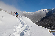 A winter hiker, wearing snowshoes, breaks trail while ascending the Old Bridle Path in the White Mountains of New Hampshire during the winter months. This trail follows the ridge in the background.