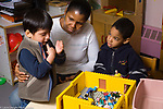 Preschool 3-5 year olds female teacher working with two boys discussing conflict or argument