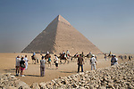 Tourists and camels at the Pyramids of Giza, with the Great Pyramid of Khufu in the background, near Cairo, Egypt.