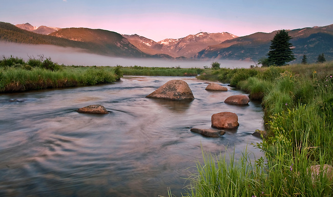 Alpenglow is reflected in the slow moving waters of the Big Thompson River in Morrain Park in Colorado's Rocky Mountain National Park.