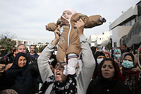 Pictured: A woman lifts her young child in protest Monday 06 February 2017<br /> Re: Scuffles between migrants and police broke out during a visit by Immigration Policy Minister Yiannis Mouzalas at the Elliniko migrant camp located in the former airport in the outskirts of Athens, Greece.