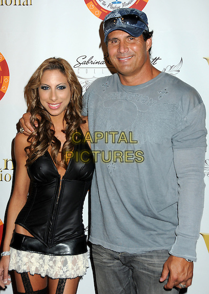 LEILA SHENNIB & JOSE CANSECO. 4th Annual Sports Dream Celebrity Poker and Pool Party Celebrating the 2010 ESPY Awards held at the Playboy Mansion, Beverly Hills, California, USA..July 12th, 2010.half length baseball cap hat grey gray affliction diesel denim sunglasses shades top leather corset dress mini white lace couple .CAP/ADM/BP.©Byron Purvis/AdMedia/Capital Pictures.