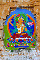 Jampelyang, Bodhisattva of Wisdom, teacher of Buddhist doctrine, holds flaming sword of awareness to cut through ignorance, and lotus, painted on the outer wall of the Potala Palace, along the Tsekor, the pilgrim circuit that encircles the Potala, Lhasa, Tibet, China..