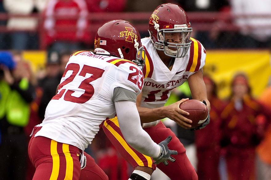 24 October 2009: Iowa State quarterback Jerome Tiller handing the ball off to running back Jeremiah Schwartz against Nebraska at Memorial Stadium, Lincoln, Nebraska. Iowa State defeats Nebraska 9 to 7.