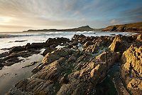 Sunset over the rocks on Porthselau Beach looking towards St David's Head, Pembrokeshire, Wales