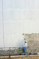 Man painting the facade of a building, Marseille, France.