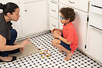 Mother and 6 year old boy in kitchen discussing broken bowl