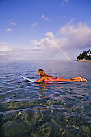 A woman in pink paddles a blue surfboard at Lahaina, Maui with a rainbow in the background.