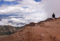 A solitary tourist, seen from the back, stands gazing out from the edge of a precipice at the top of Pike's Peak near Colorado Springs, CO, while clouds boil up in his face. A carpet of storm clouds two miles below can be seen spreading to the horizon. August 2006. clouds, cumulus, cumulonimbus, cloudbank, Colorado, mountains, sky, landscape, scenery, vacation, travel