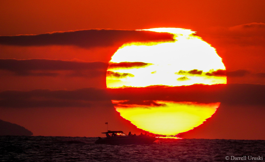 Sunrise on the Pacific. Landscape photograph of a yacht sailing on the Pacific ocean in front of a very large sun that is setting on the ocean.<br /> <br /> This photograph was from the shoreline located in Puerto Vallarta Mexico.