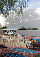 A white plastic table and stools are set outside in the courtyard terrace. Colourful rugs strewn on ground gives the area an informal air.