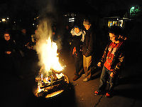 STAFF PHOTO ANDY SHUPE - Residents place evergreen branches on a bonfire during a celebration of the winter solstice Sunday, Dec. 21, 2014, at the Unitarian Universalist Fellowship of Fayetteville.