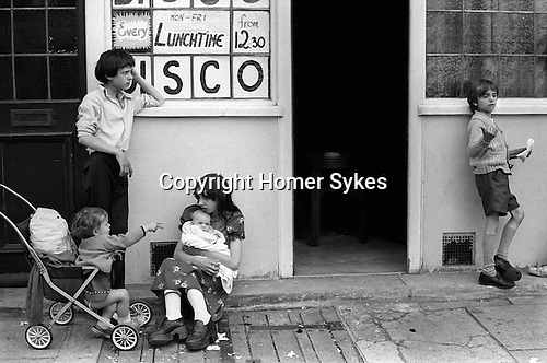 Children, siblings, brother and older sister look after family babies. They are waiting outside a Lunch Time Disco pub for their parents to re emerge. Elephant and Castle, SE London 1970s UK..