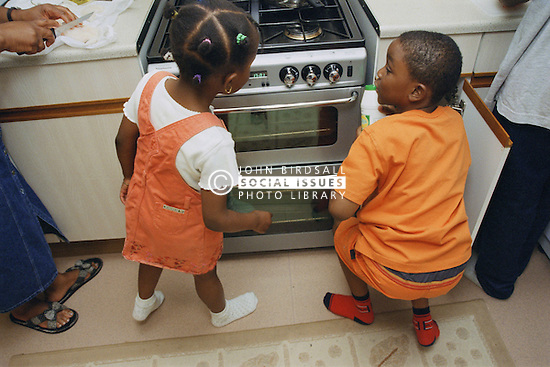 Two young children standing next to cooker in kitchen,