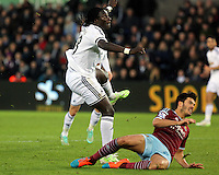 Pictured L-R: Bafetimbi Gomis of Swansea has his shot stopped by a West Ham defender Saturday 10 January 2015<br />